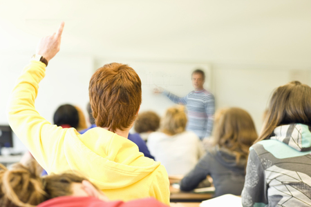Male high school student raising hand to ask question in class