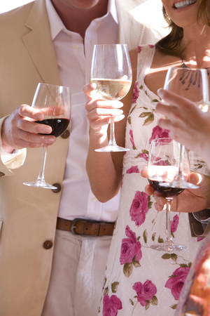Detail of couples holding wine glasses of red and white wine