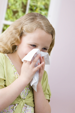 Young girl with cold sneezing and blowing nose on tissue