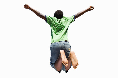 Cut out of active boy jumping in air arms outstretched