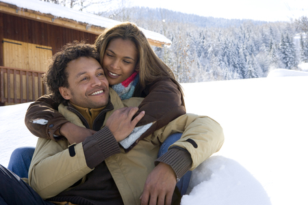 Loving couple hugging in snow outside chalet on winter vacation