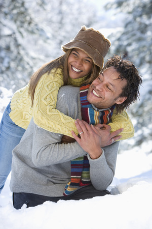 Loving couple hugging in snow on winter vacation