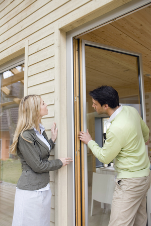 Couple checking hinge on external door at home