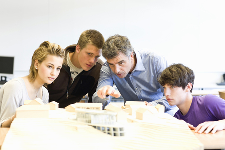 Male teacher and teenage high school students with architectural model Imagens