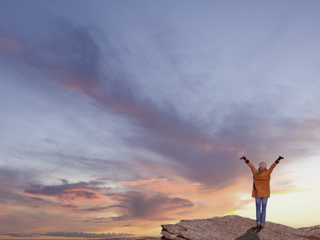 Adventurous woman standing on rocky cliff against dramatic sunset 스톡 콘텐츠
