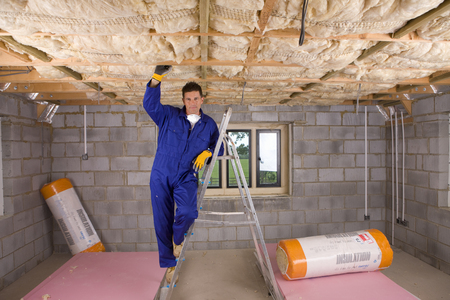 Construction worker in overalls fitting insulation into roof at camera Stock Photo