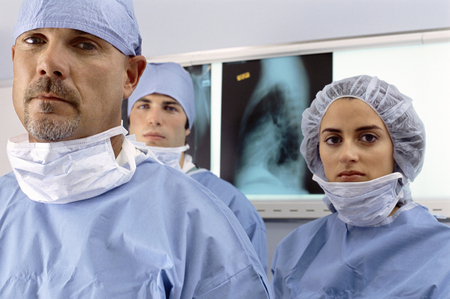 Hospital surgical team in scrubs standing in front of x-rays looking at camera Imagens