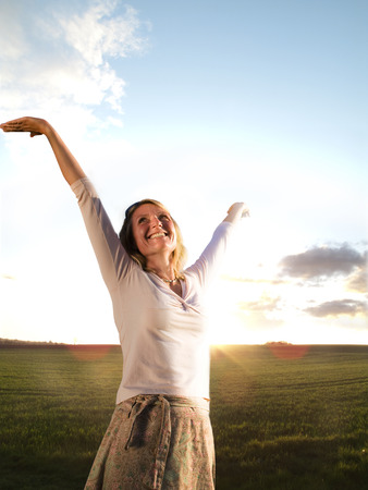 Smiling woman standing in field with arms outstretched at sunset Stok Fotoğraf