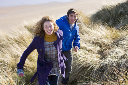 Loving young couple running through dunes on winter beach smiling at camera Banco de Imagens