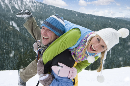 Man carrying woman on back through falling snow on winter vacation smiling at camera