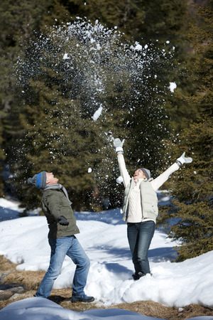 Smiling senior couple on winter vacation throwing snow in air on walk Imagens
