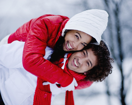 Man giving woman piggyback on snowy winter day smiling at camera