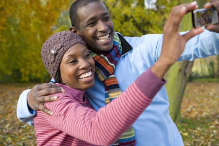 Smiling couple taking selfie with cell phone on walk in autumn park