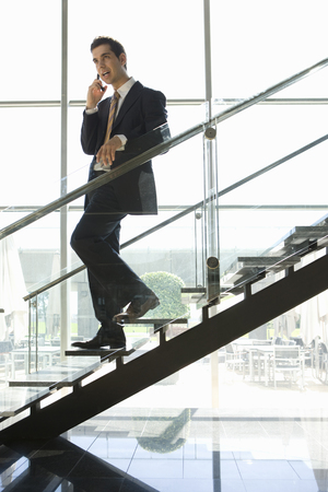 Businessman talking on cell phone walking down office stairs Stock Photo