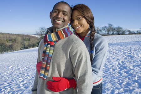 Loving couple on winter vacation hugging on snowy hill smiling at camera