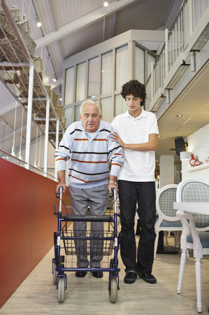 Young man helping senior male resident in care home using walker