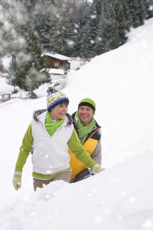 Loving couple on winter vacation walking in falling snow