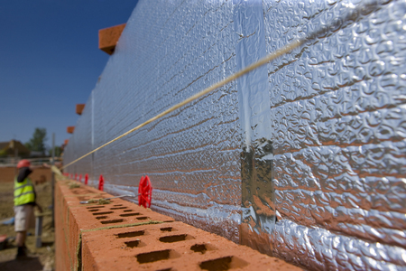 Insulation installed in brick wall on construction site