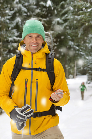 Hiker with compass in woods in falling snow smiling at camera Stock Photo