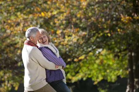 Loving senior couple hugging on walk through autumn countryside