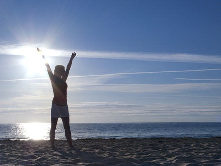 Silhouette of woman with outstretched arms standing on beach