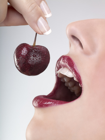 Studio close up of womans mouth eating fresh cherry Reklamní fotografie