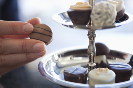 Detail of woman taking a chocolate from a sweet stand Stock Photo