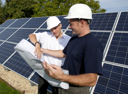 Engineers discussing plans standing next to large solar panels Banco de Imagens