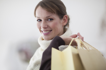Woman in store carrying bags on shopping trip smiling at camera