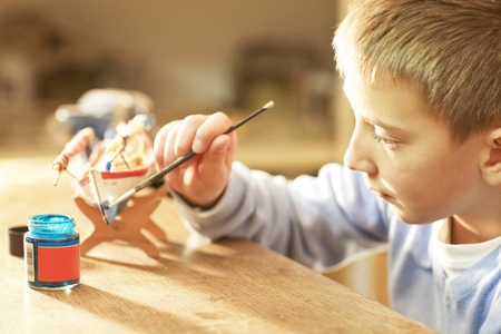 Young boy at home painting wooden model boat