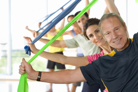 Men and women with resistance bands in exercise class smiling at camera 写真素材