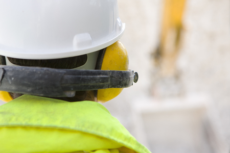 Construction worker wearing protective hard hat and ear defenders