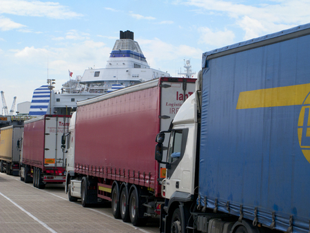 Freight trucks in line waiting to board ferry boat at port