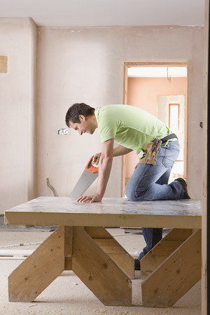 Carpenter with saw cutting timber inside house on construction site Stock Photo