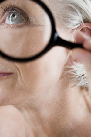 Beauty concept with senior woman holding magnifying glass against skin Stock Photo