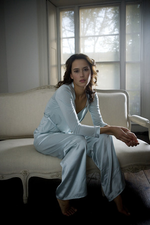 Young woman wearing silk pajamas sitting on sofa at home looking at camera
