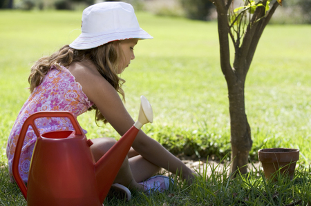 Young girl watering and caring for plant in garden Banco de Imagens - 119750292