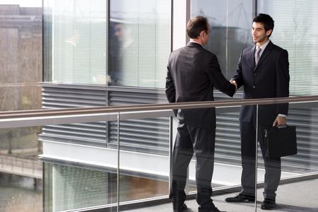 Two businessmen shaking hands on walkway in modern office Stockfoto - 119750626