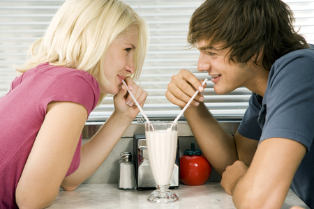 Teenage couple on date sharing milkshake in café