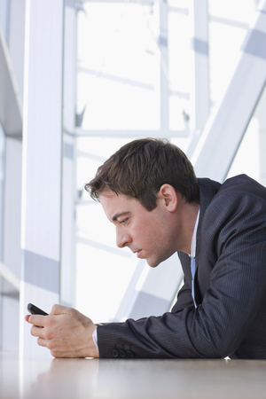 Businessman reading text message on cell phone in office lobby Stock Photo