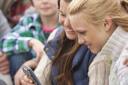Group of teenage girls reading text message on cell phone