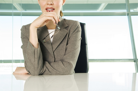 Detail of businesswoman sitting at boardroom table holding glasses Banco de Imagens