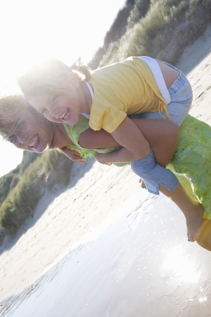 Portrait of mother piggybacking daughter on beach Stock Photo