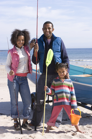Portrait of family holding fishing nets on beach