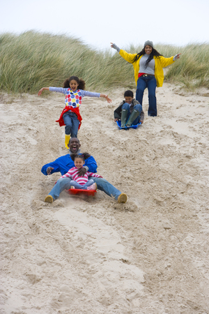 Family playing with sleds on beach slope