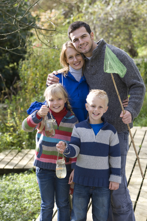 Family with bug net and specimen jars outdoors