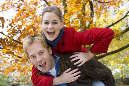 Husband giving woman piggyback ride outdoors