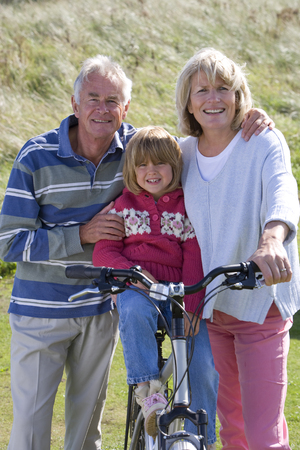 Portrait of grandparents with granddaughter sitting on bicycle