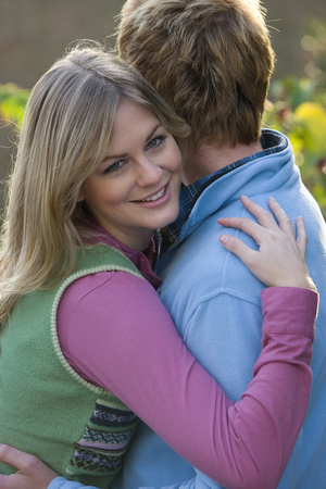 Smiling woman hugging husband