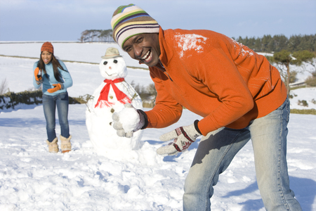 Couple with snowman in snowy field Stock Photo